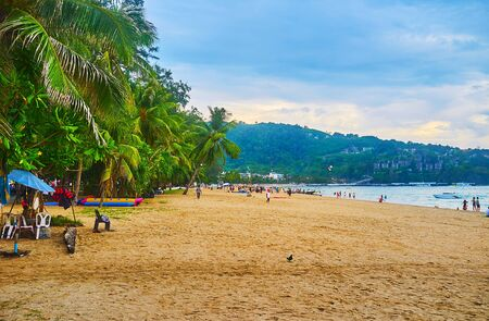 The central beach of Patong with line of lush tropical greenery, hiding beach bars, water scooter rental points and other tourist spots, Phuket, Thailand