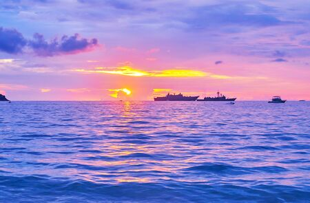 The fiery sunset over the calm waters of Andaman sea, reflecting the purple sky and bright rays of sun, Patong, Phuket, Thailand Reklamní fotografie