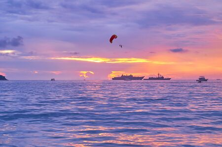 The parasailing parachute, flying in bright sunset sky over the purple waters of Andaman sea, Patong, Phuket, Thailand
