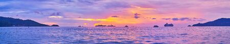 Panorama of the Patong coast on sunset with silhouettes of the ships, cruise liner and dark blue clouds on the bright purple sky, Phuket, Thailand Reklamní fotografie