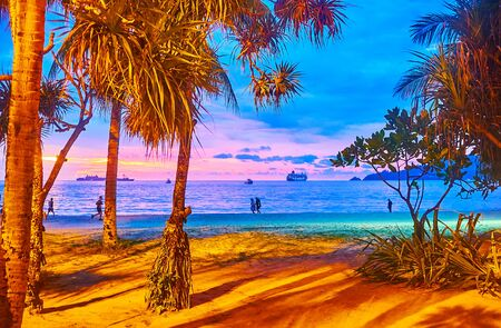 The pleasant evening walk along the beach of Patong with illuminated tropical trees and bright twilight sky with ships silhouette on horizon, Phuket, Thailand Reklamní fotografie