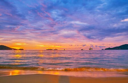 Walk the tideline of Patong beach on sunset and watch the scenic cloudscape, last sunlight and ships on the distance, Phuket, Thailand