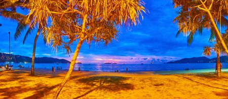 Panorama of the evening beach through the tropical trees in bright lights, Patong, Phuket, Thailand 版權商用圖片