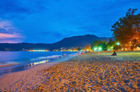 Enjoy romantic evening walk along the coast of Patong beach and gentle tide of Patong bay, Phuket, Thailand