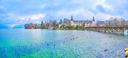 The scenic panoramic view on Traun lake with mauntains on the background and medieval Orth Landschloss castle with old wooden bridge, Gmunden, Austria Zdjęcie Seryjne