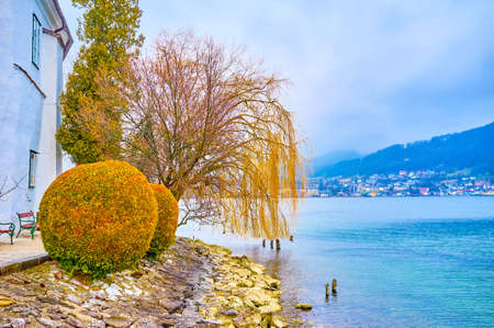 The tiny walking area around Schloss Ort castle islet with a view on surrounding landscapes of Traun lake, Gmunden, Austria Imagens - 151357299