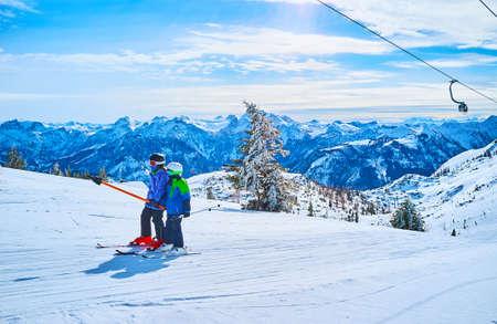 Two little kids use the button ski lift to reach the top of training ski zone, Feuerkogel Mountain plateau, Ebensee, Salzkammergut, Austria Imagens - 151357300