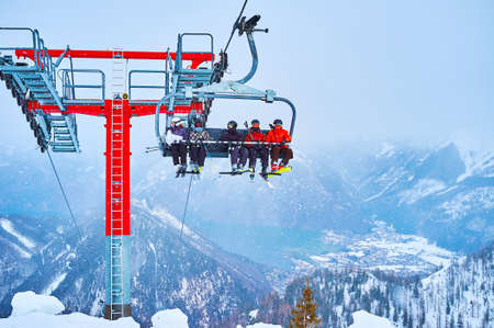 The heavy snowfall in misty Dachstein Alps, the Feuerkogel mount overlooks the  Traunsee lake and fast riding chairlift