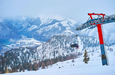 Watch misty Traunsee valley from the snowy slope of Feuerkogel mount with its chairlifts, pistes and pine forests on snowfall, Ebensee, Salzkammergut, Austria