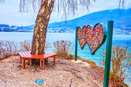 The popular above youth the romantic bench at the edge of the islet in Traun lake with the sculpture of the heart, decorated with colorful love locks, Gmunden, Austria Imagens - 151357845