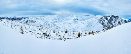 Panorama with heavy clouds over the Feuerkogel Mountain plateau, gentle rocky hills, snowshoe tracks and small spruce trees in snow Salzkammergut, Austria 版權商用圖片