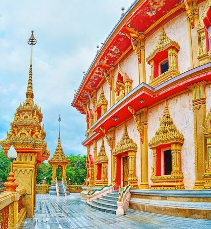 The facade wall of Wat Chalong Chedi, richly decorated with gilt carved window frames and door frames, Naga serpents on stairs balusters, Chalong, Phuket, Thailand