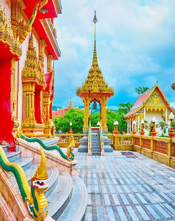 The small court in front of Wat Chalong Chedi with green Naga serpents on stairs' balusters and tall pavilion of mondop, topped with spire and hti umbrella, Chalong, Phuket, Thailand