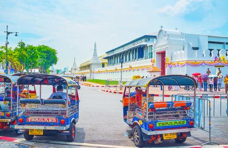 BANGKOK, THAILAND - APRIL 15, 2019: The taxi tuk-tuk rickshaws stand at the Grand Palace's exit and wait for tourists, on April 15 in Bangkok Editorial