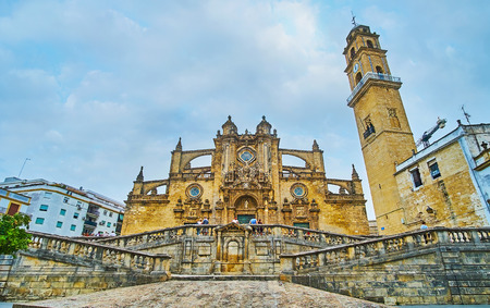 JEREZ, SPAIN - SEPTEMBER 20, 2019: The medieval architectural ensemble of Holy Saviour Cathedral with complex staircase, scenic facade with flying buttresses, carvings, sculptures and tall bell tower, on September 20 in Jerez
