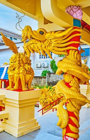 The dragon column of Sam Sae Chu Hut Chinese Shrine with carved golden roaring serpent, Phuket City, Thailand
