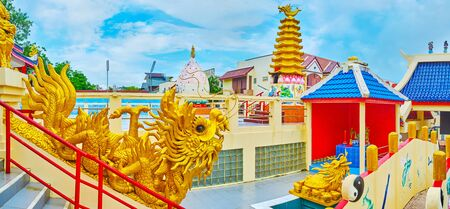 PHUKET, THAILAND - APRIL 30, 2019: Panorama the courtyard of Sam Sae Chu Hut Chinese Shrine with golden dragons, running along balusters, turtle-dragon in pond and firecracker tower on the background, on April 30 in Phuket