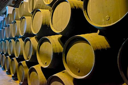 Explore solera wine ageing process and watch the row of stacked black sherry casks on the ground of old winery, Jerez, Spain