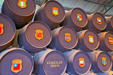 JEREZ, SPAIN - SEPTEMBER 20, 2019: Close-up of the casks in Real Bodega de la Concha of Tio Pepe winery with flags of countries, where Gonzalez Byass wines are exported, on September 20 in Jerez Editorial