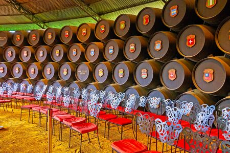 JEREZ, SPAIN - SEPTEMBER 20, 2019: The row of stacked sherry casks in vintage Real Bodega de la Concha of Tio Pepe winery; the flags on casks belong to the countries-importers of Gonzalez Byass wines, on September 20 in Jerez Editorial