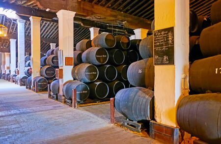 JEREZ, SPAIN - SEPTEMBER 20, 2019: Interior of wine museum of Bodegas Tio Pepe winery with stacked sherry casks, marked with Gonzalez Byass brand, on September 20 in Jerez