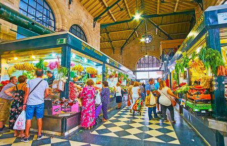 JEREZ, SPAIN - SEPTEMBER 20, 2019: Mercado Central de Abastos (Sentral Abastos Market) produce division with large variety of fresh fruits and vegetables in small stalls, on September 20 in Jerez