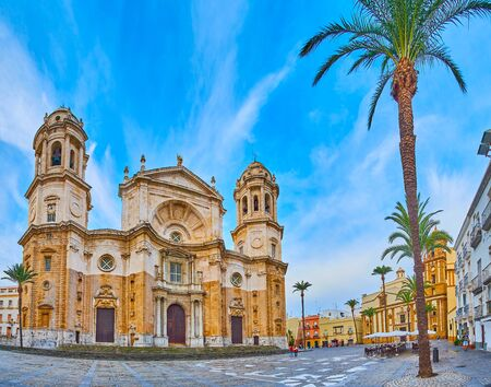 Panorama of Cathedral Square (Plaza de la Catedral) with historical landmarks, such as Cadiz Cathedral, Church of Santiago Apostol and colored townhouses, Spain Фото со стока