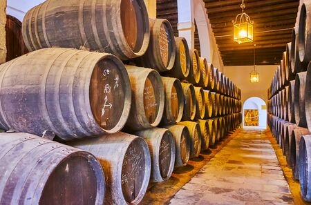 JEREZ, ESPAGNE - 20 SEPTEMBRE 2019 : Les vieux fûts empilés avec des signatures de visiteurs célèbres dans la cave La Constancia de Bodegas Tio Pepe, le 20 septembre à Jerez