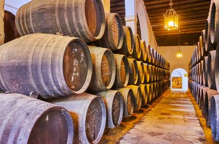 Jerez, SPANIEN - 20. SEPTEMBER 2019: Die alten gestapelten Fässer mit Unterschriften berühmter Besucher im Weingut La Constancia von Bodegas Tio Pepe, am 20. September in Jerez