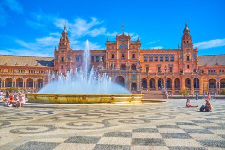 SEVILLE, SPAIN - OCTOBER 1, 2019: The large fountain in the middle of Plaza de Espana is the most beloved place for relaxing under the refreshing sprays, on October 1 in Seville