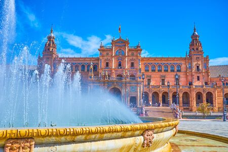 SEVILLE, SPAIN - OCTOBER 1, 2019: The large fountain on Plaza de Espana with refreshing cool water is one of the most beloved objects on the large and hot open area, on October 1 in Seville