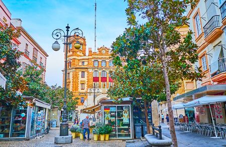 CADIZ, SPAIN - SEPTEMBER 20, 2019: The Plaza de Las Flores (Flower Square) with lush shady trees, small flower stalls, outdoor cafes, vintage streetlights and building of Post Office on the background, on September 20 in Cadiz