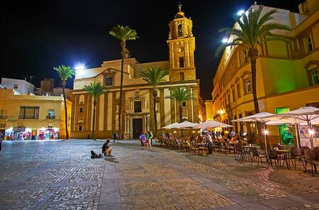 CADIZ, SPAIN - SEPTEMBER 20, 2019: Enjoy the evening walk along Cathedral Square with a view on Santiago Apostol Church and small outdoor cafes, on September 20 in Cadiz Editoriali