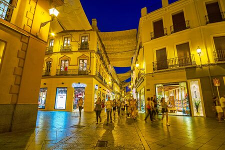 SEVILLE, SPAIN - OCTOBER 1, 2019: The local youth walk along shopping streets at night, passing bright showcases of numerous boutiques and stores, on October 1 in Seville