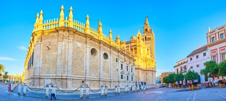 SEVILLE, SPAIN - OCTOBER 1, 2019: Panoramic view on the side walls of the Cathedral and tourist carriages standing along the buildings on Plaza del Triunfo, on October 1 in Seville