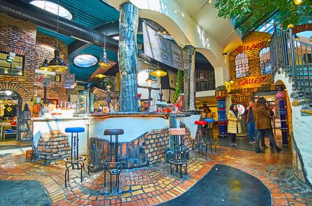 VIENNA, AUSTRIA - FEBRUARY 19, 2019: The unique architecture and variety of souvenir stores attract tourists to visit Hundertwasser Village - modern bizarre complex in city, on February 19 in Vienna Redactioneel