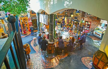 VIENNA, AUSTRIA - FEBRUARY 19, 2019: The lounge zone of Hundertwasser Village with interesting stone bar counter, decorated with narrow fountain, making air fresh and cool, on February 19 in Vienna