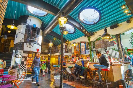 VIENNA, AUSTRIA - FEBRUARY 19, 2019: The Hundertwasser village lounge zone with bar and cafe, popular among the tourists, visiting local handicraft market, on February 19 in Vienna