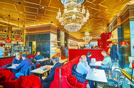 VIENNA, AUSTRIA - FEBRUARY 19, 2019: Famous Viennese Sacher cafe is always crowded, locals and tourists enjoy Wiener melange with traditional desserts (sacher cake, strudel), on February 19 in Vienna