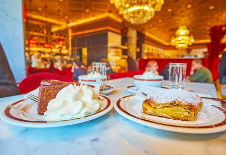 VIENNA, AUSTRIA - FEBRUARY 19, 2019: Delicious chocolate Sacher cake (Sachertorte) and apple strudel with whipped cream in splendid Sacher cafe -popular Wiener coffee house, on February 19 in Vienna