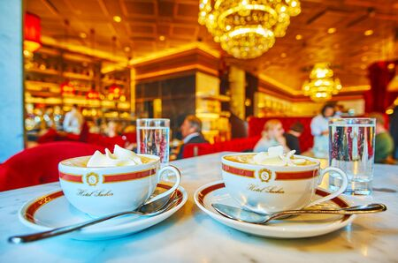 VIENNA, AUSTRIA - FEBRUARY 19, 2019: Enjoy tasty Wiener Melange coffee drink with whipped cream, posh interior and atmosphere of famous Sacher cafe - typical Wiener coffee house, located next to Opera House, on February 19 in Vienna