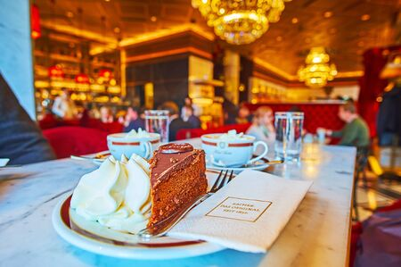 VIENNA, AUSTRIA - FEBRUARY 19, 2019: Visit traditional Vienese Sacher cafe and enjoy tasty chocolate Sacher cake (Sachertorte) with whipped cream, on February 19 in Vienna Redactioneel