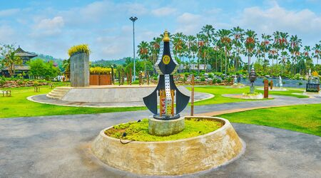CHIANG MAI, THAILAND - MAY 7, 2019: Panorama of Grand amphitheater of Rajapruek Royal Park with modern sculptures, ornamental lawn, small scene and palm alley on background, on May 7 in Chiang Mai
