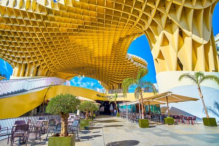 SEVILLE, SPAIN - OCTOBER 1, 2019: The entrance to the restaurant of Metropol Parasol complex with the outdoor terraces on the ground floor, on October 1 in Seville