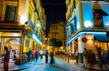 SEVILLE, SPAIN - OCTOBER 1, 2019: Night is a very crowded time, tourists and locals walk around the streets and cafes and restaurants become full, on October 1 in Seville Editorial