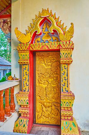 The carved wooden door with colorful doorframe, decorated with fine patterns, Naga serpents and mirror mosaic, Wat Phra That Mae Yen temple, Pai, Thailand