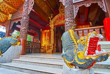 The facade of Vihara (shrine) with intricate carved patterns, gilt entrance, columns and statues of mom mythic aquatic creatures, Wat Phra That Doi Suthep temple, Chiang Mai, Thailand Stock Photo