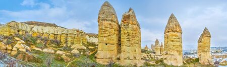Panoramic vista of tall finger-like rock formations, known as fairy chimney rocks of Goreme, Cappadocia, Turkey