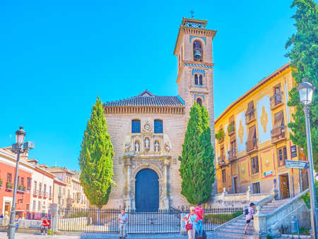 GRANADA, SPAIN - SEPTEMBER 25, 2019: The facade of medieval San Gil and Santa Ana church is decorated with carved stone sculptures, relief patterns and Mudejar tilling on belfry, on September 25 in Granada Editorial