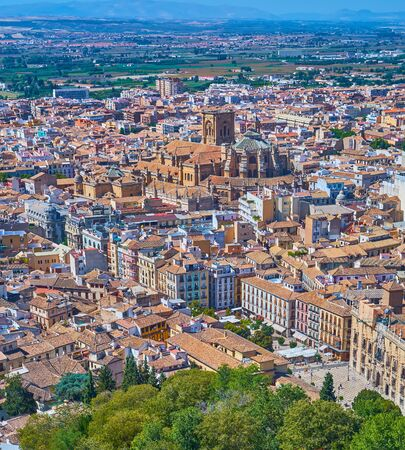 Enjoy the top view of Granada city center with Plaza Nueva square, Calle Reyes Catolicos street, old tile roofs and Gothic Cathedral of Granada, Spain